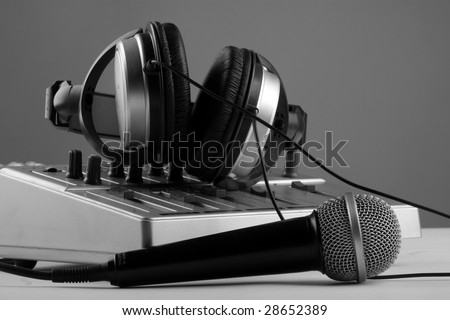 microphone with mixer and headphones in sound studio - stock photo