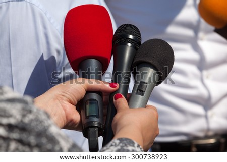 Microphones. Reporters taking interview at news conference. - stock photo