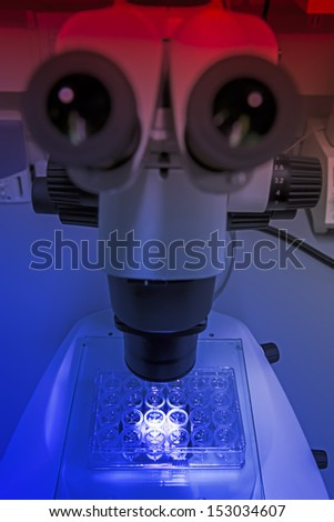 Microscope at a chemical laboratory in the mystical blue red light - stock photo