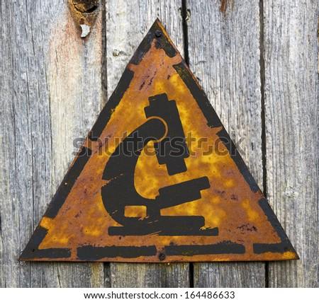 Microscope Icon on Weathered Triangular Yellow Warning Sign. Grange Background. - stock photo