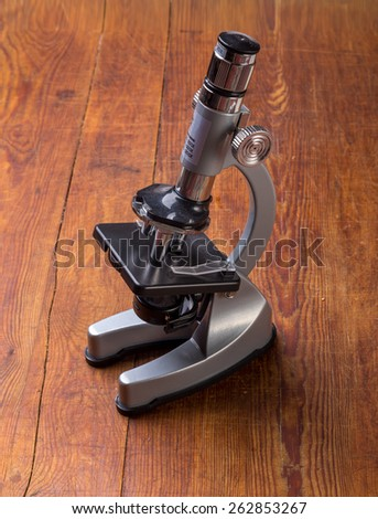 Microscope on table for vintage science background - stock photo