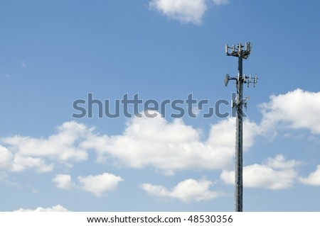 Microwave and cellular tower with partly cloudy blue sky - stock photo