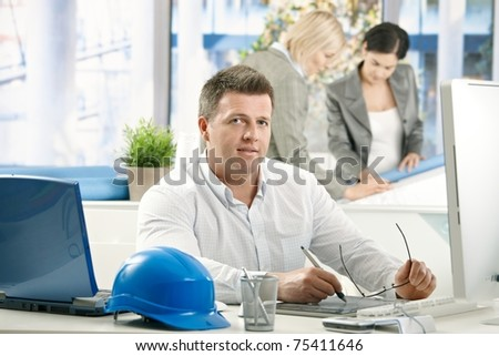 Mid-adult architect working in office, looking at camera, busy coworkers in background.? - stock photo