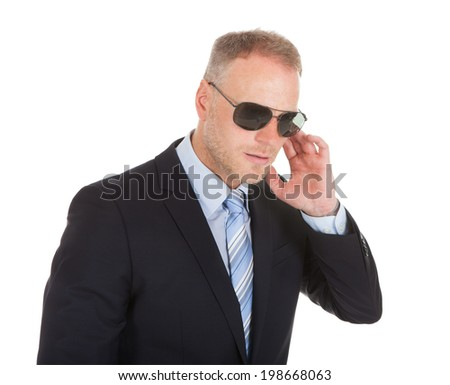 Mid adult bodyguard wearing sunglasses isolated over white background - stock photo