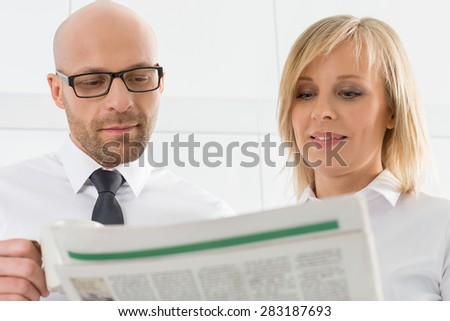 Mid adult business couple reading newspaper in kitchen - stock photo