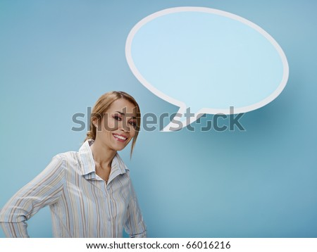 mid adult business woman standing near blank speech bubble on blue background. Horizontal shape, front view, waist up, copy space - stock photo