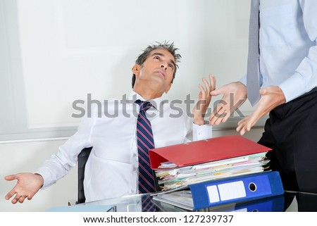 Mid adult businessman at desk overwhelmed by load of work - stock photo