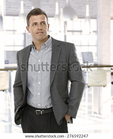 Mid-adult businessman at office, looking away. - stock photo