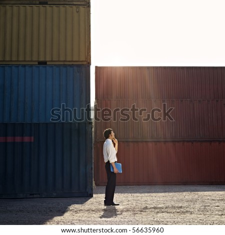 Mid adult businessman standing near cargo container with hand on chin and looking up. Square shape, full length, side view, copy space - stock photo