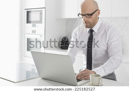 Mid adult businessman using laptop at kitchen counter - stock photo