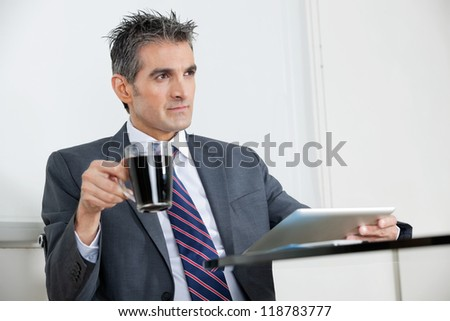 Mid adult businessman with coffee cup using digital tablet at desk in office - stock photo