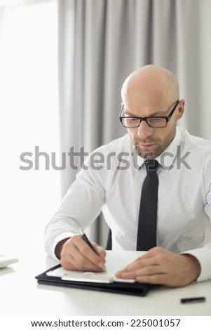 Mid adult businessman writing on clipboard in home office - stock photo