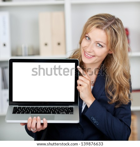 Mid adult businesswoman displaying laptop with blank screen in office - stock photo