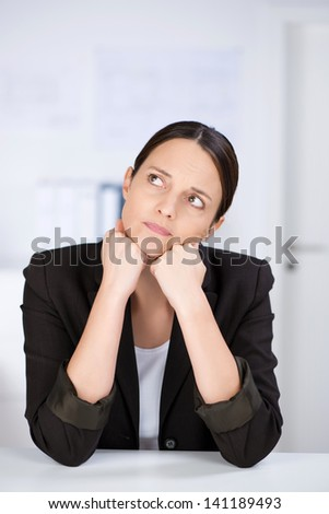 Mid adult businesswoman looking away while leaning on desk - stock photo