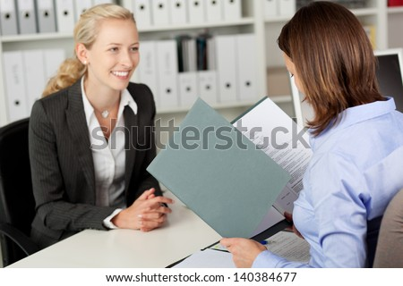 Mid adult businesswoman reading female candidate's CV at office desk - stock photo