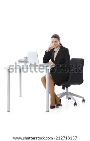 Mid-adult businesswoman working at desk, using laptop computer, smiling, cutout on white, full length. - stock photo