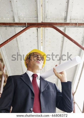 mid adult caucasian architect holding blueprints in construction site. Vertical shape, low angle view, waist up - stock photo