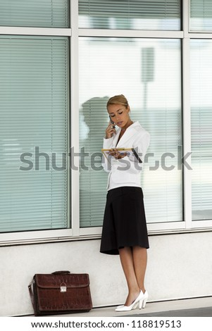 mid adult caucasian business woman talking on mobile phone and reading documents near office building wall. Full length - stock photo