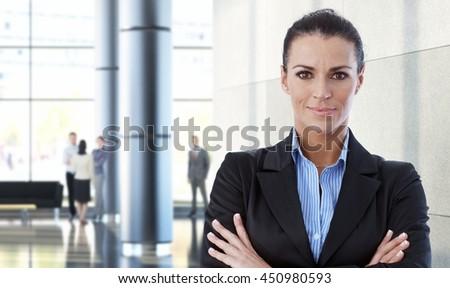 Mid-adult caucasian businesswoman indoors in office building. - stock photo