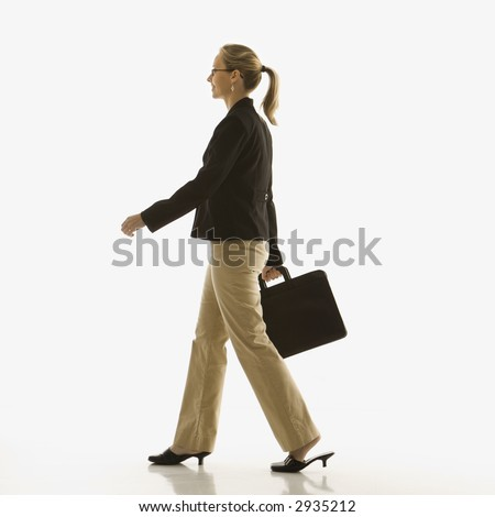 Mid-adult Caucasian businesswoman walking and carrying briefcase. - stock photo
