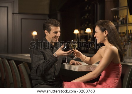 Mid adult Caucasian couple at bar toasting wine glasses and smiling. - stock photo