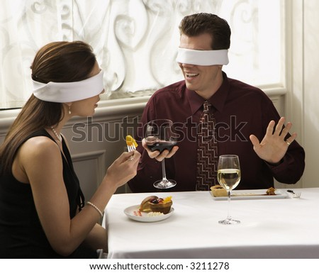 Mid adult Caucasian couple dining in a restaurant with blindfolds over eyes. - stock photo