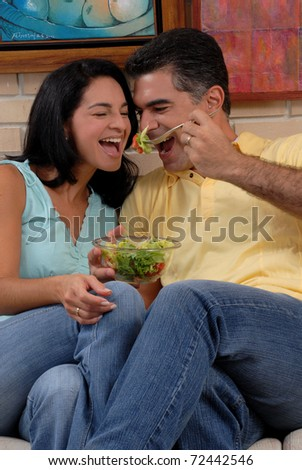 Mid adult couple eating and sharing in a living room. - stock photo