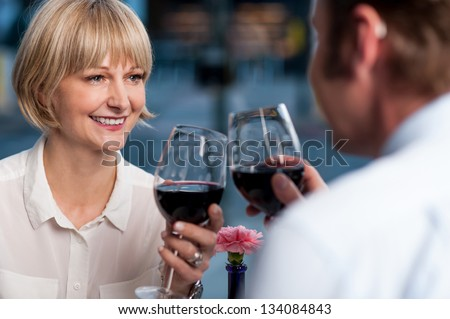 Mid adult couple toasting in restaurant. Cheers to our love. - stock photo