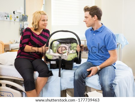 Mid adult couple with baby carrier looking at each other while sitting on hospital bed - stock photo