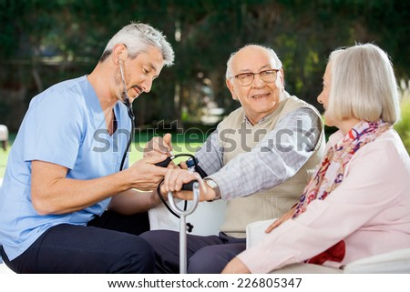 Mid adult doctor measuring blood pressure of senior man sitting beside woman at nursing home porch - stock photo