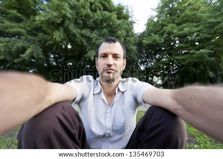 Mid adult (early 30's) caucasian man looking at the camera with an enigmatic confident gaze photographing himself at the park. - stock photo