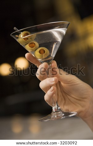 Mid adult female Caucasian hand holding a martini with three olives. - stock photo