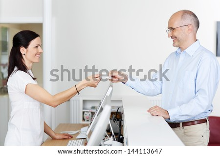 Mid adult female receptionist receiving card from patient in dentist clinic - stock photo