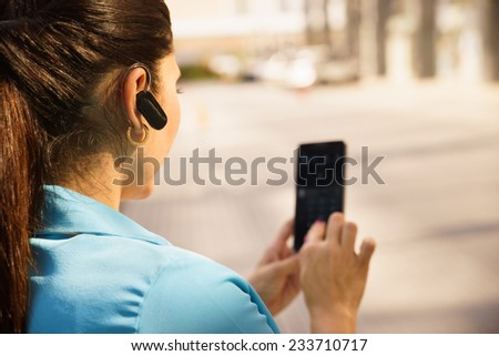 Mid adult hispanic person with mobile phone and bluetooth headset, typing on telephone in the street - stock photo