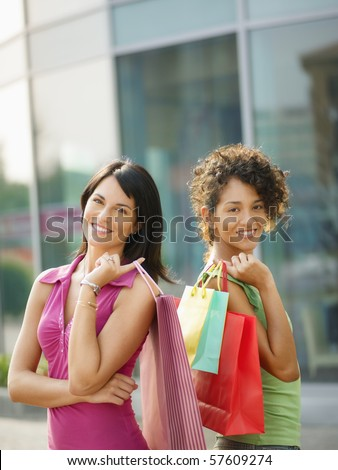 mid adult italian woman and hispanic woman carrying shopping bags out of shopping center. Vertical shape, waist up, copy space - stock photo