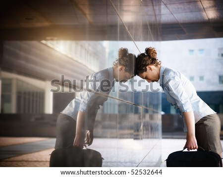mid adult italian woman banging her head against a wall outside office building. Horizontal shape, copy space - stock photo