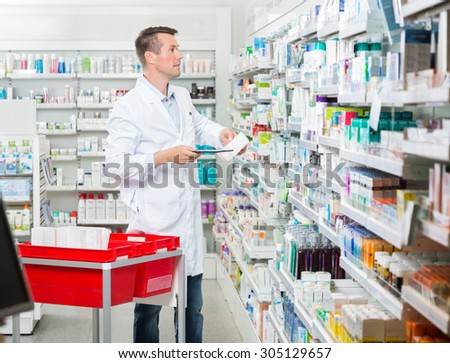 Mid adult male pharmacist counting stock while holding tablet computer at pharmacy - stock photo