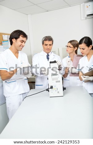 Mid adult male scientist analyzing sample in medical laboratory - stock photo
