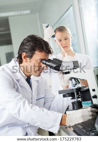 Mid adult male scientist using microscope with colleague working in background - stock photo