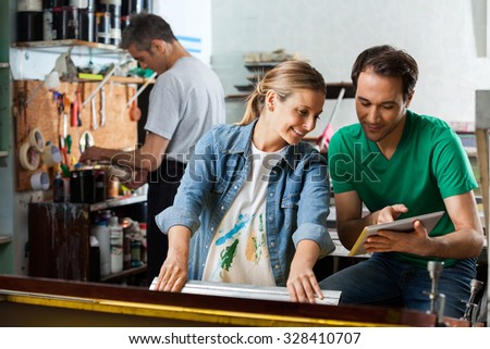 Mid adult male supervisor showing design on tablet computer to female employee using squeegee in paper factory - stock photo