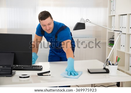 Mid adult male worker cleaning desk with sponge at office - stock photo