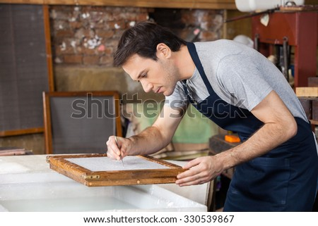 Mid adult male worker using tweezers to clean paper in factory - stock photo