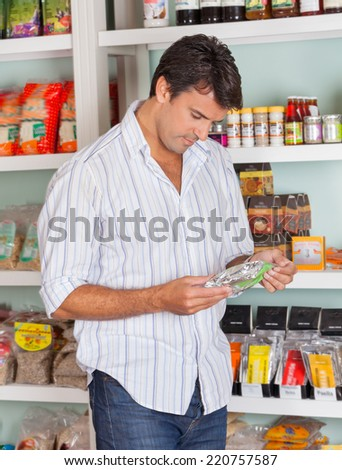 Mid adult man choosing product in grocery store - stock photo