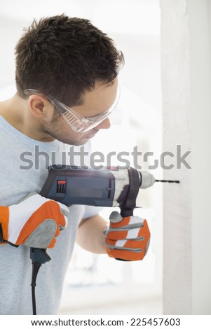 Mid-adult man drilling in wall - stock photo
