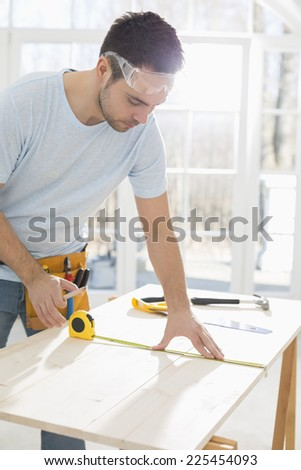 Mid-adult man marking table with measure tape - stock photo