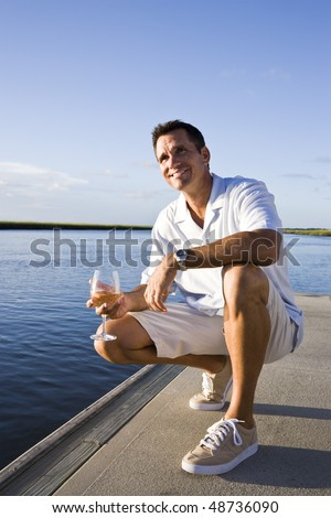 Mid-adult man on dock by water enjoying drink on sunny day - stock photo