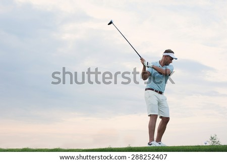 Mid-adult man playing golf against sky - stock photo