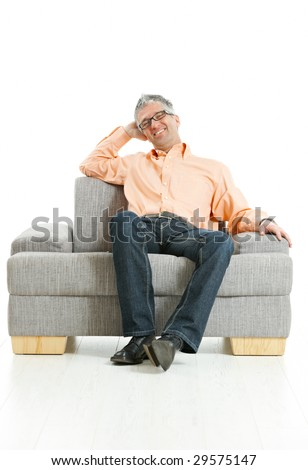 Mid-adult man wearing jeans and orange shirt sitting on couch, talking on mobile phone. Isolated on white. - stock photo