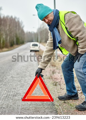 Mid adult man wearing reflector vest and he have a red warning triangle - road and vehicle on background - stock photo
