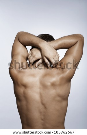 Mid adult man with hands behind head (rear view) - stock photo